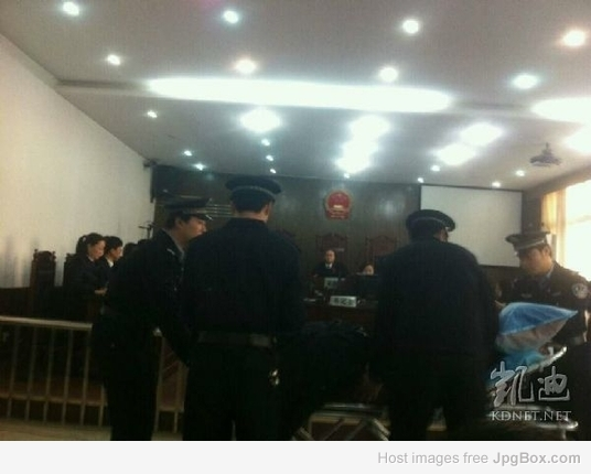 桂松/图片说明:桂松在担架上受审...